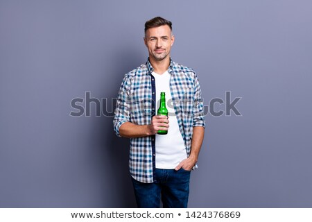 Hansome amusing man with beard holding bottle of beer  Stock photo © deandrobot
