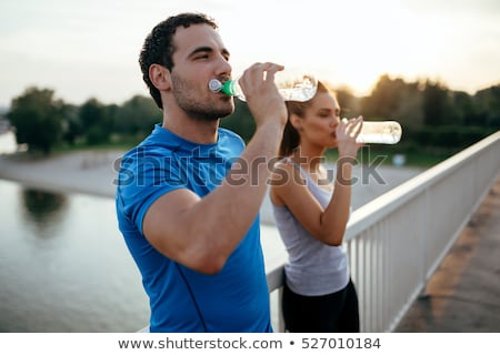 Young sporty man athlete resting after jogging and drinking water Stock photo © deandrobot