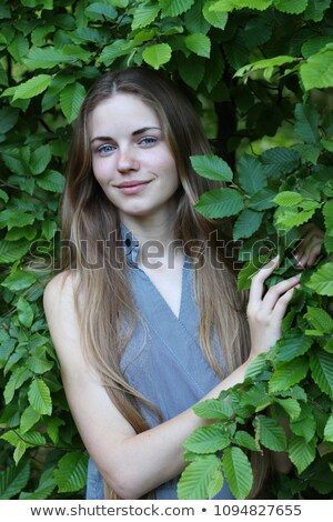 Attractive tender young woman surrounded by green leaves Stock photo © deandrobot