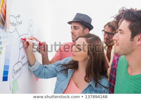 Creative team watching coworker add to flowchart Stock photo © wavebreak_media