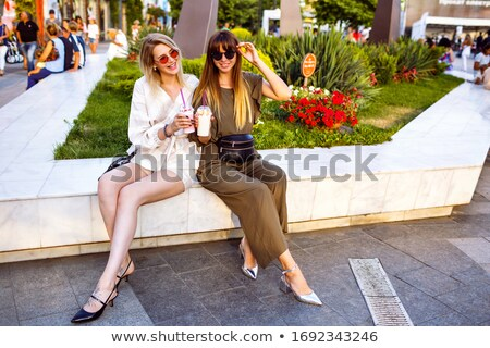 Smiling trendy young woman on a marble bench Stock photo © dash