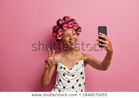 Cheerful lady posing over dark background make peace gesture. Stock photo © deandrobot