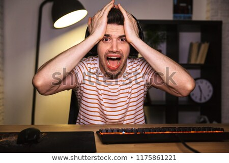 portrait of stressed gamer guy grabbing head while playing video stock photo © deandrobot