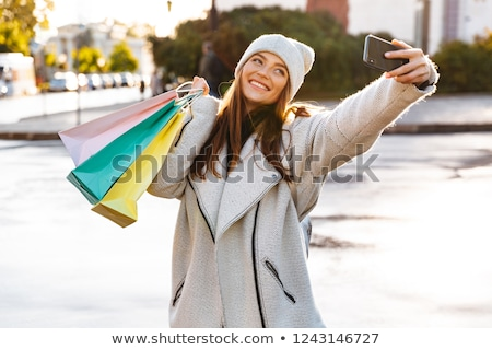 redhead happy woman walking outdoors holding shopping bags take a selfie by mobile phone stock photo © deandrobot