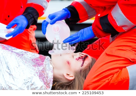 Emergency doctor giving oxygen to accident victim Stock photo © Kzenon