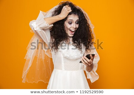 surprised happy bride zombie using smartphone and smiling isolated stock photo © deandrobot