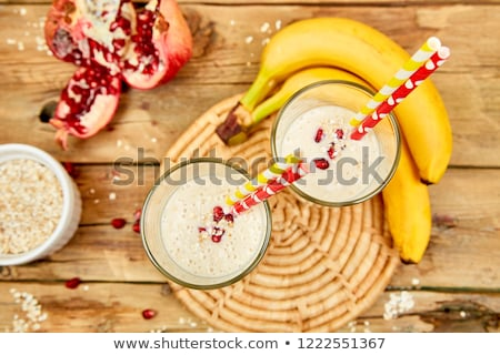 Smoothie with oat or oatmeal, banana and pomegranate on wooden rustic background. Stock photo © Illia