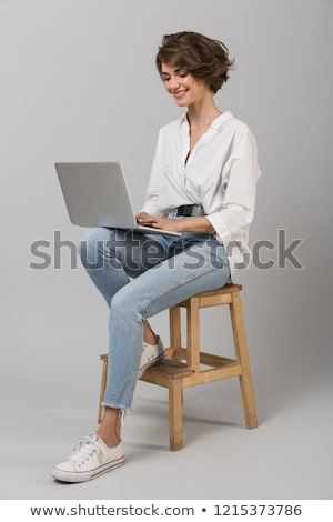 Young business woman posing isolated over grey wall background sitting on stool using laptop compute Stock photo © deandrobot
