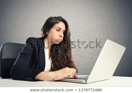 Bored woman snorts in the office while working on the laptop Stock photo © alphaspirit