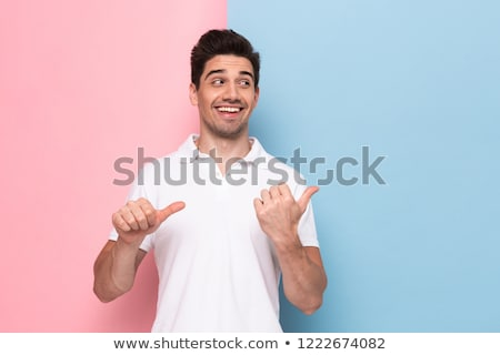 Image of cheerful man 30s having stubble pointing fingers aside  Stock photo © deandrobot