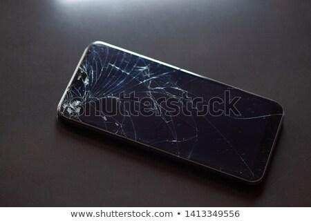 Smartphone with broken touchscreen on black desktop Stock photo © adamr