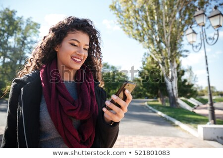Woman outdoors using mobile phone looking aside. Stock photo © deandrobot