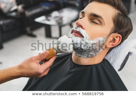 Hairdresser applying cream for shaving Stock photo © Kzenon
