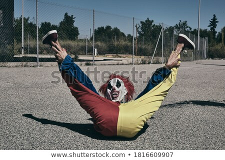 scary evil clown sticking out his tongue outdoors stock photo © nito