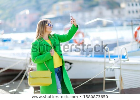 Beautiful woman tourist near the yacht during the journey, calls his travel agent Stock photo © ElenaBatkova