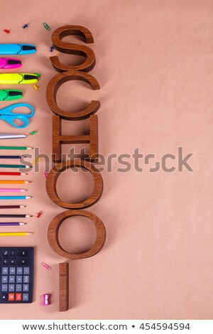 Inscription school near stationery on blue background. Back to School. Frame, copy space. Top view.  Stock photo © Illia