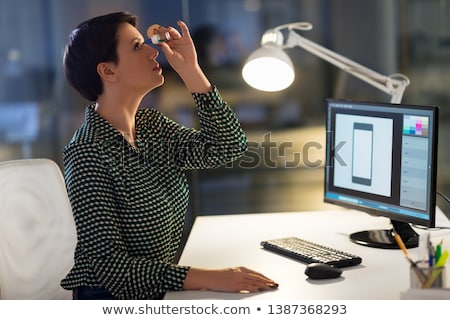 businesswoman using eye drops at night office Stock photo © dolgachov