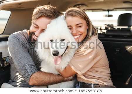 Stock photo: Loving couple with dog samoyed outdoors at the beach.
