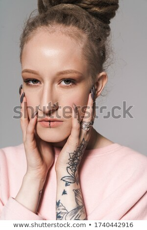 Concentrated young girl with dreadlocks, piercing and tattoos Stock photo © deandrobot