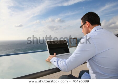 man with computer in front of the sea stock photo © photography33