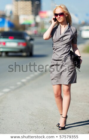 Stockfoto: Young Woman With Cell Phone Walking Blured Business Building In