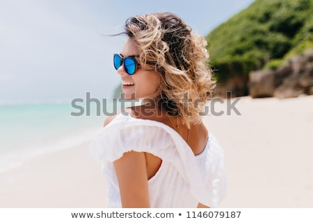 Beautiful woman in dress with wavy hair on sea beach background, Stock photo © Victoria_Andreas