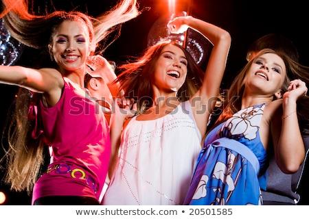 three smiling women dancing in the club stock photo © dolgachov