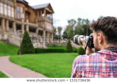Photographer taking pictures with SLR camera Stock photo © Maridav