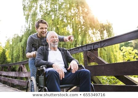 Foto stock: Pai · caminhada · inválido · filho · cadeira · de · rodas · parque
