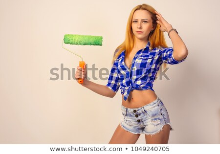 Stock photo: Pretty girl in shorts and shirt holding paint roller
