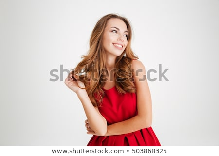 Smiling woman in red dress looking away Stock photo © deandrobot