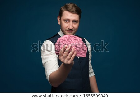 Stock photo: Handsome young man magician showing tricks with playing cards