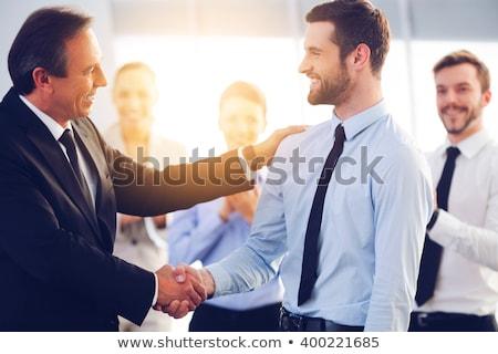 dos · empresarios · apretón · de · manos · sonriendo · hombre - foto stock © deandrobot