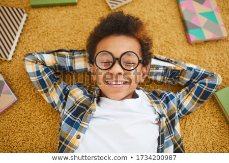 Cheerful boy lies on floor while look at the camera. Stock photo © deandrobot