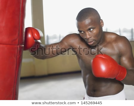 agressive shirtless african american man athlete standing and boxing stock photo © deandrobot