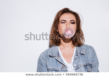 playful lady blowing bubble with chewing gum stock photo © deandrobot