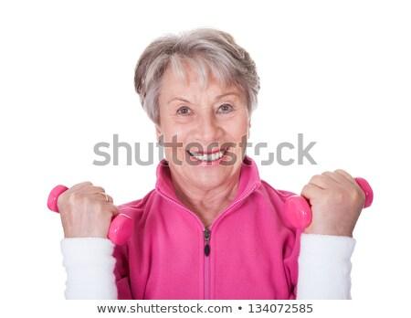 Smiling trainer assisting senior woman with hand raised Stock photo © wavebreak_media
