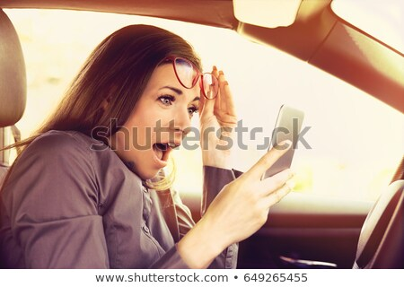 amazed woman distracted reading a message on cellphone driving a car stock photo © ichiosea