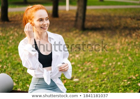happy young sports lady standing with earphones stock photo © deandrobot