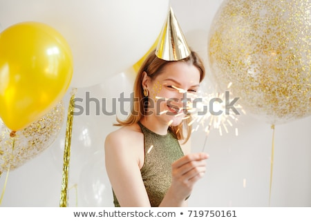 Young woman in a celebratory cap fooling around at a party on the background of balloon stock photo © Sibstock