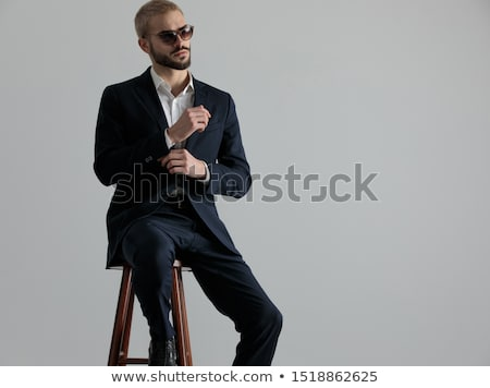 cool modern man fixing his sleeve and looks away  Stock photo © feedough