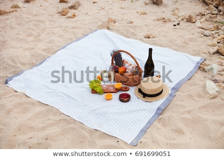 Picnic on the beach at sunset in the white plaid, food and drink stock photo © Yatsenko