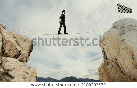 Business concept of businessman who overcome the problems reaching the flag on a rope Stock photo © alphaspirit
