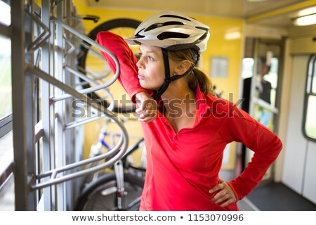 pretty young female biker traveling on a train with her bike stock photo © lightpoet