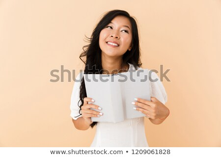 Portrait of a dreamy asian girl isolated over beige Stock photo © deandrobot