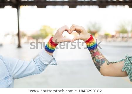 gay couple with rainbow wristbands and hand heart Stock photo © dolgachov