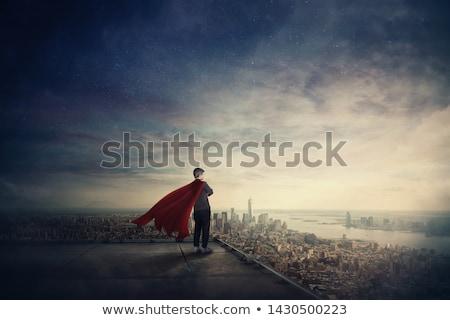 businesswoman in superhero cape over city sunset Stock photo © dolgachov