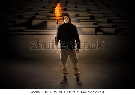 Stock fotó: Man Coming With Burning Flambeau From The Maze Concept