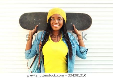 smiling teenage girl with skateboard over white stock photo © dolgachov
