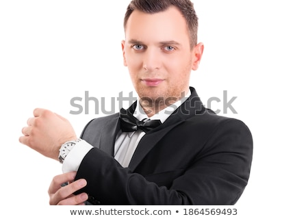 young groom buttoning up his cuffs and looking into the camera Stock photo © feedough